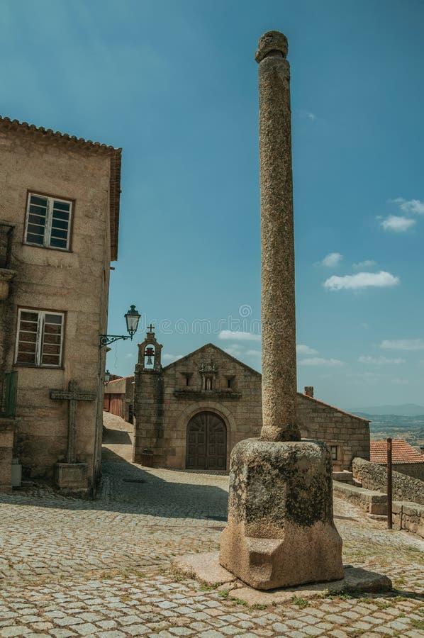 Kamienny pręgierz przed starym kościół z dzwonem w Monsanto obrazy royalty free