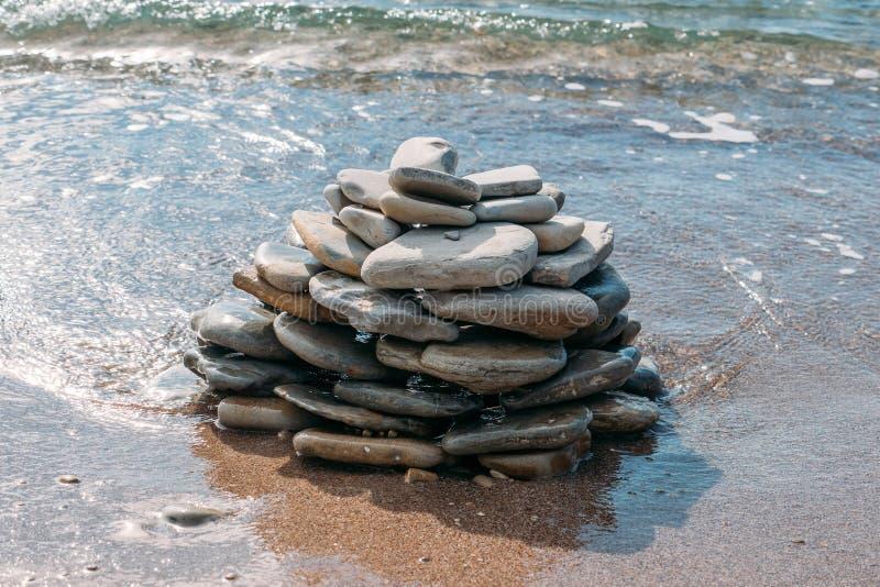 Kamienny wierza na dennym wybrzeżu lub plażowa pobliska woda na piasku, lato inspiracji tło zdjęcie royalty free