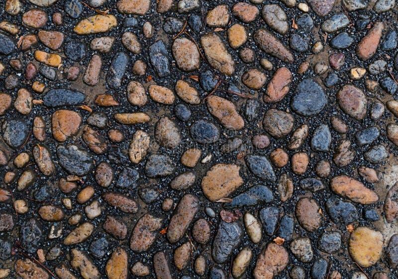 Kamiennych kanwa gładkich owalnych kamieni brown szarzy kamienie mini na czarnego tła piaska zakończenia bazaltowym wzorze mocno  obrazy royalty free