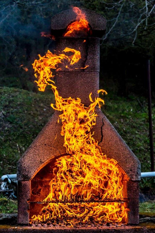 Kamin mit enormem Feuer und Teufel von den Flammen aufgedeckt stockfoto