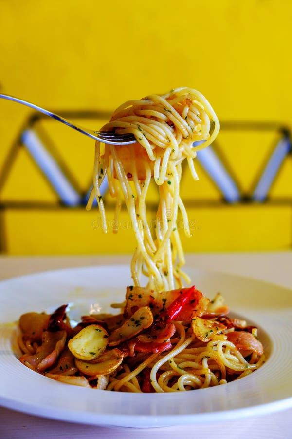 Kamma hem spagetti med gaffeln royaltyfri fotografi