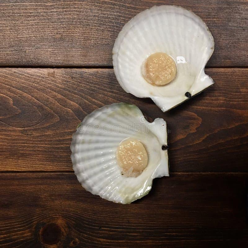 Kammmuschelfleisch ist im Oberteil auf einer dunklen hölzernen Tabelle lizenzfreie stockfotos