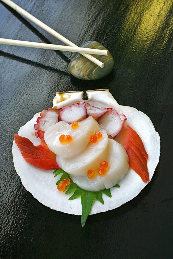 Kammmuscheln, die Sashimi gesehen wird, dienten mit Thunfisch auf einer Muschelschale stockfoto