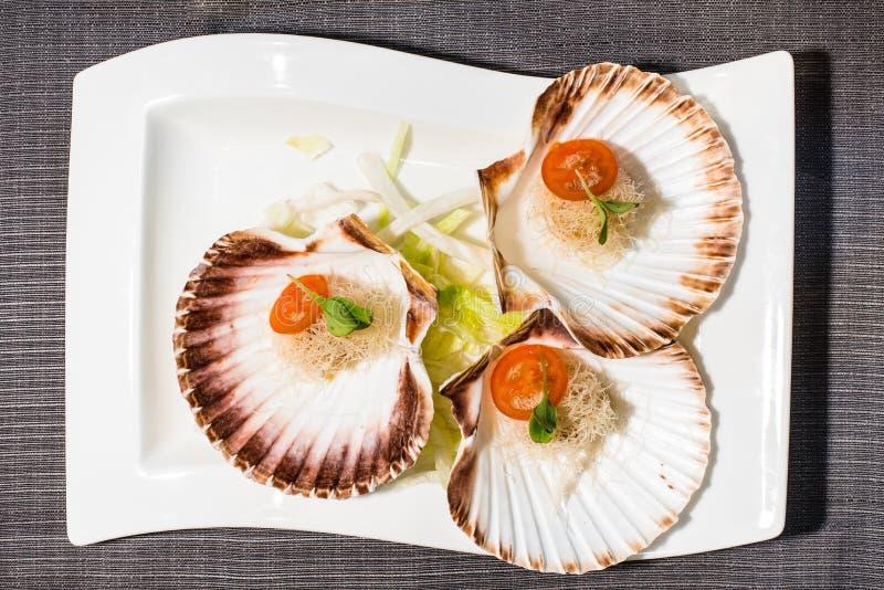 Kammosselen in shells met kersentomaten en salade die worden gediend stock foto