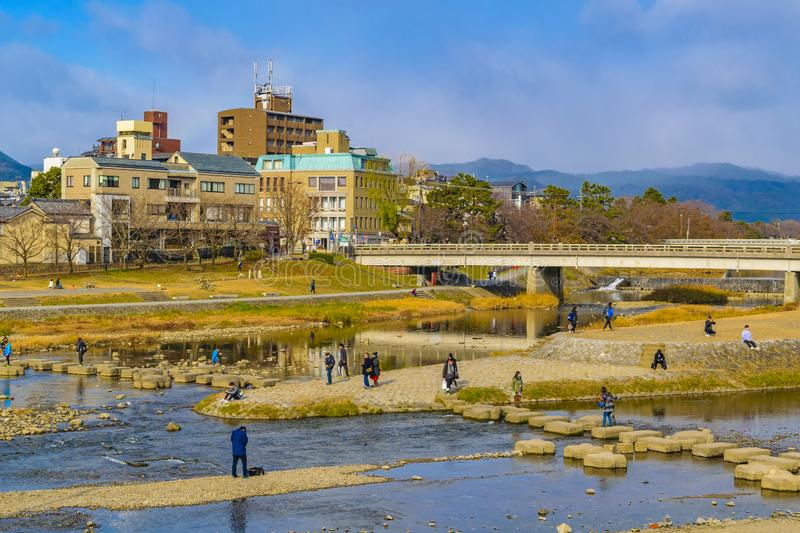 Kamo River, Kyoto, Japan. KYOTO, JAPAN, JANUARY - 2019 - People enjoying a sunny winter day at kamo river in kyoto city, japan royalty free stock image