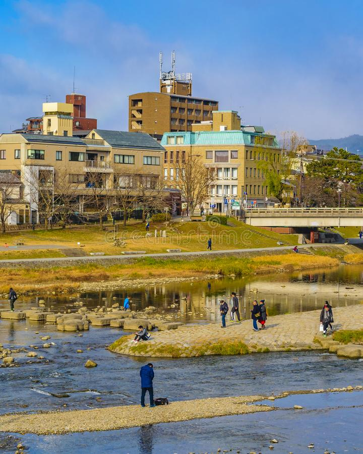 Kamo River, Kyoto, Japan. KYOTO, JAPAN, JANUARY - 2019 - People enjoying a sunny winter day at kamo river in kyoto city, japan stock image