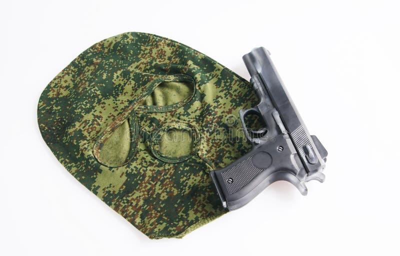 Kamouflagemaskering och en handeldvapen arkivbilder
