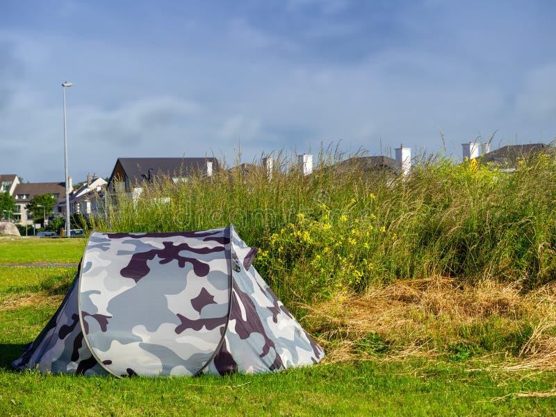 Kamouflagetält i ett fält vid husgodset, begreppshemlös, rikt och fattigt arkivbilder