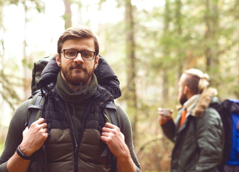 Kamp, avonturen, het reizen en vriendschapsconcept Mens met een rugzak en een baard en zijn vriend die in bos wandelen royalty-vrije stock afbeelding