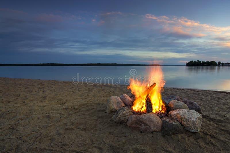Kampbrand op zandig strand, naast meer bij zonsondergang Minnesota, de V royalty-vrije stock afbeelding