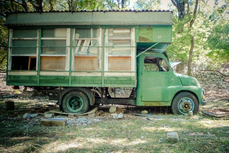 Kampeerautovrachtwagen in het hout wordt verlaten dat Oude gesloopte auto in het voorste gedeelte royalty-vrije stock foto's