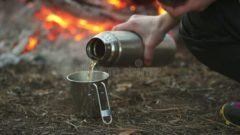 Kampeerautovrouw het kamperen giet thee van een thermosfles en het drinken in bos dichtbij brand