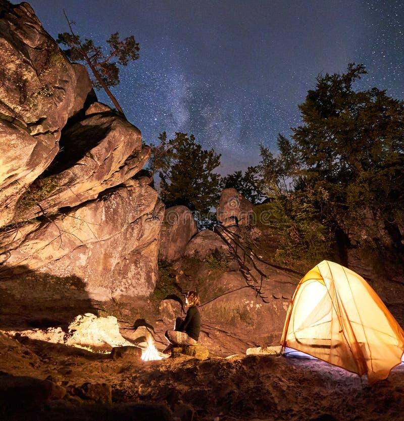 Kampeerterrein bij nacht amid reusachtige steile rotsvormingen Aantrekkelijke meisjeszitting op kei bij vuur royalty-vrije stock foto