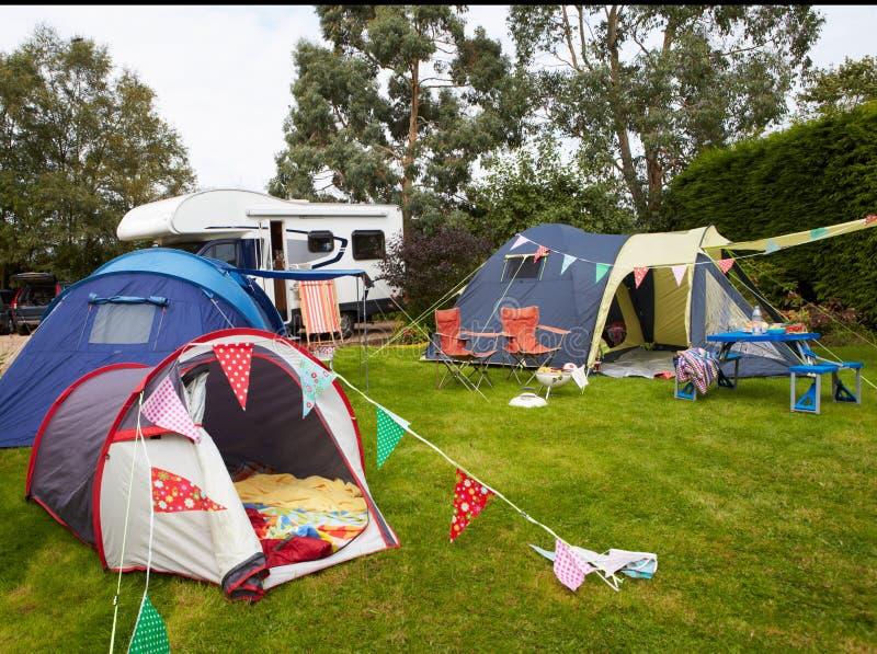 Kampeerterrein met Geworpen Tenten en Campervan stock afbeelding
