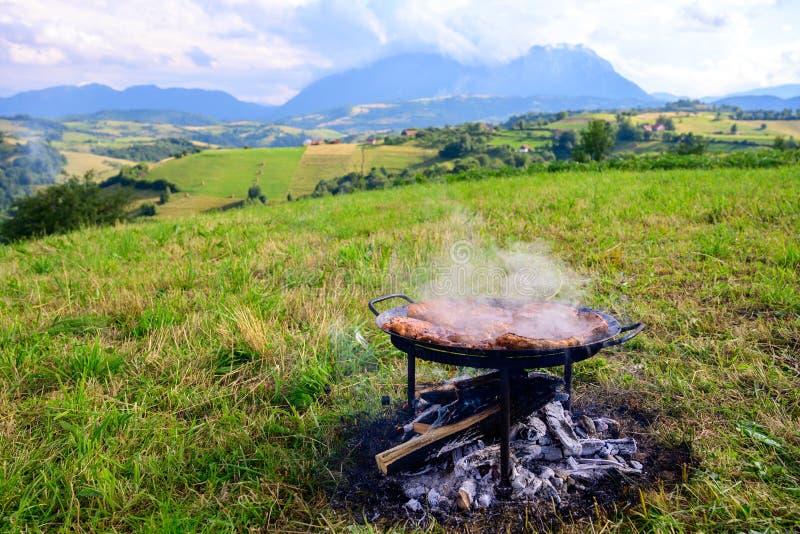 Kamperend in aard, die voedsel op traditionele barbecue, de zomervakantie voorbereiden royalty-vrije stock foto