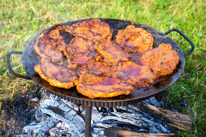 Kamperend in aard, die voedsel op traditionele barbecue, de zomervakantie voorbereiden stock afbeeldingen