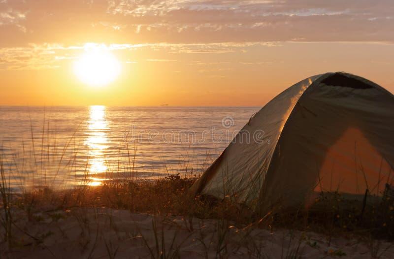 Kamperend bij zonsondergang op het overzees, toeristentent op het strand stock foto