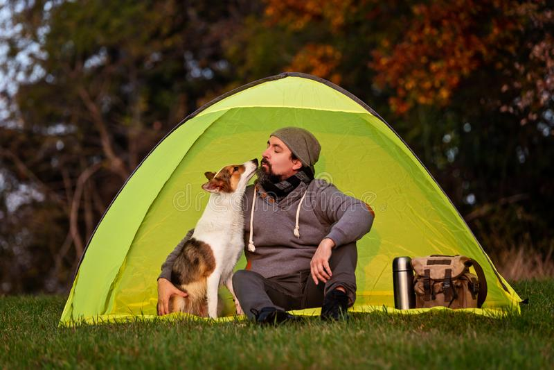 Kamperend met het huisdier, vriendschap tussen de mens en zijn hond royalty-vrije stock afbeelding
