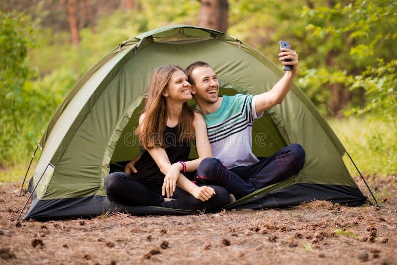 Kamperend paar in tent die selfie nemen Gelukkige vrienden die pret hebben togheter Conceptenlevensstijl en technologie royalty-vrije stock foto's