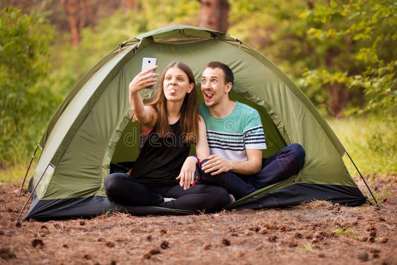 Kamperend paar in tent die selfie nemen Gelukkige vrienden die pret hebben togheter Conceptenlevensstijl en technologie stock afbeelding