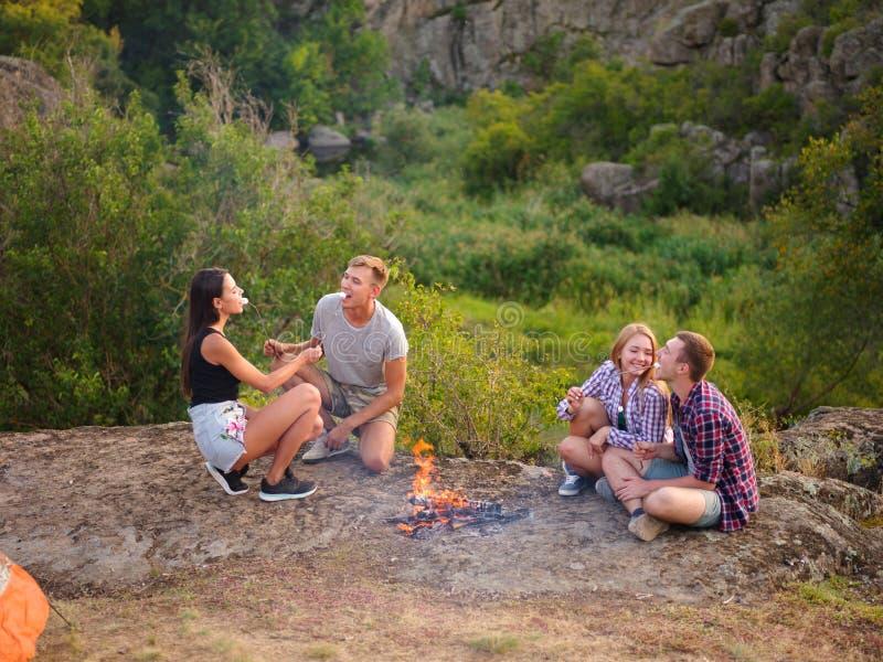 Kamperende studenten dichtbij vuur op een natuurlijke achtergrond Leuke paren die heemst eten Het concept van de picknickdag De r stock afbeelding