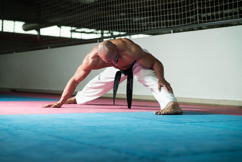 Kampfkünste bemannen im Kimono, der Karate ausübt stockbild
