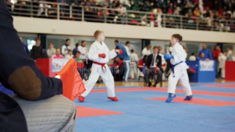 Kampfkunstwettbewerbskarate - beurteilen Sie die Trainer, die weiblichen Jugendlicher ` s Karate Fighting betrachten stockfoto