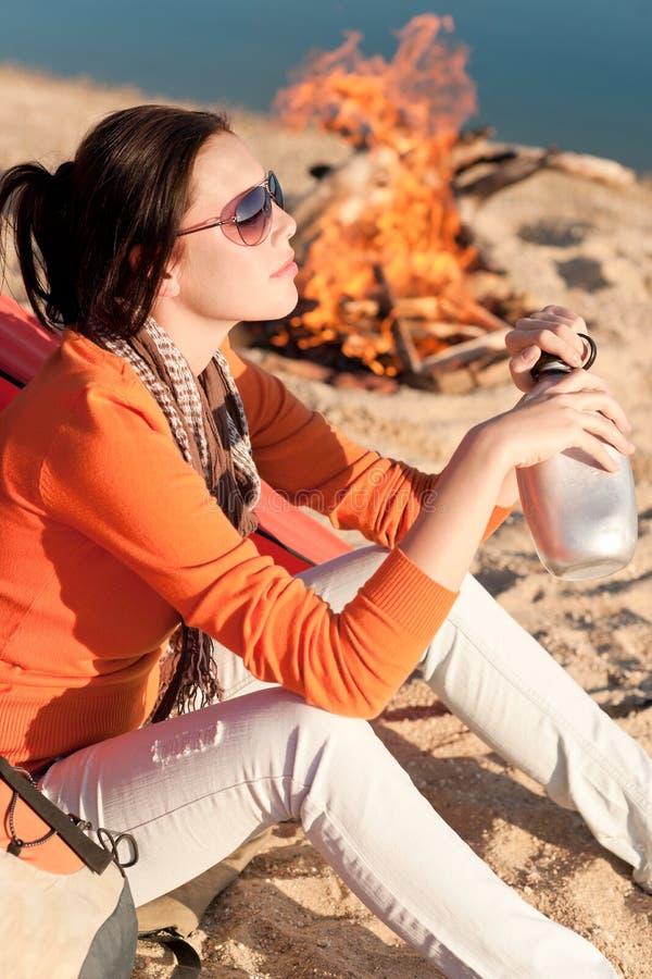 Kampierende glückliche Frau durch Lagerfeuer auf Strand lizenzfreie stockfotografie