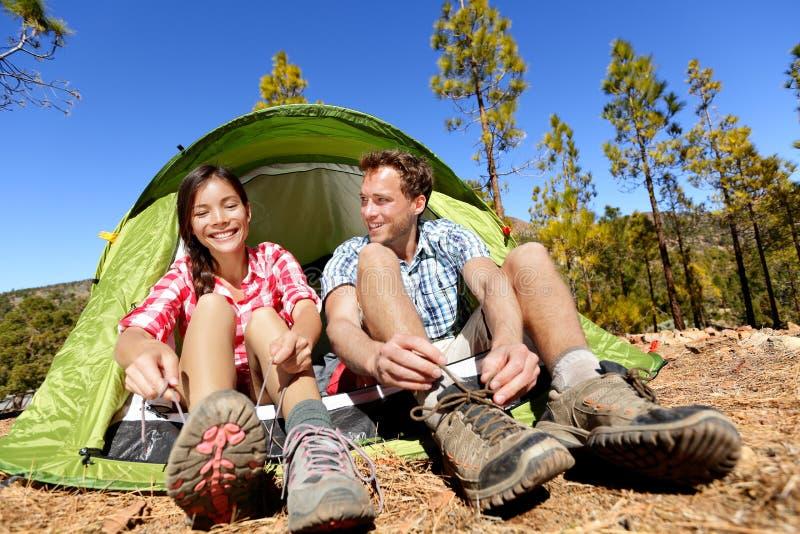 Kampierende Leute, die auf dem Wandern von Schuhen durch Zelt sich setzen stockbild