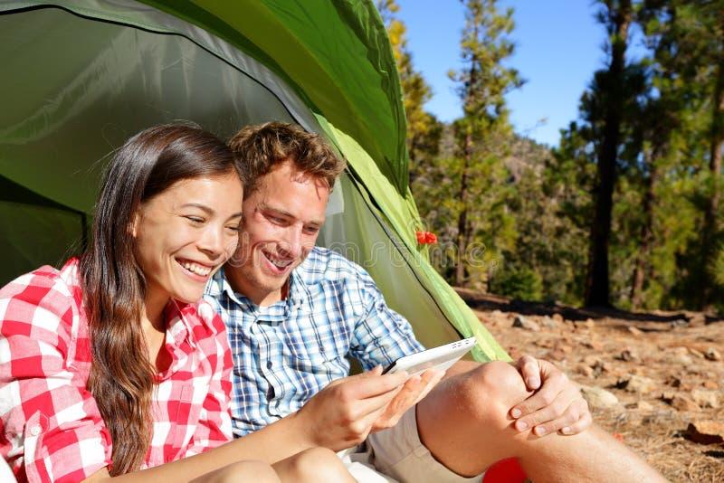 Kampierende Paare im Zelt unter Verwendung des Smartphone lizenzfreies stockbild