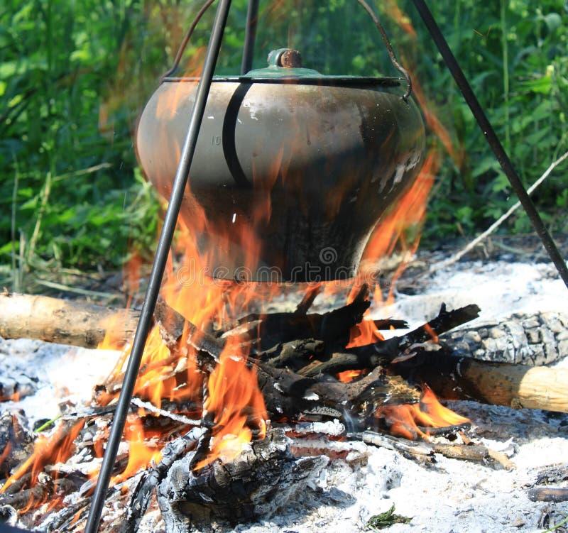 Kampierender Kessel über brennendem Lagerfeuer lizenzfreie stockbilder