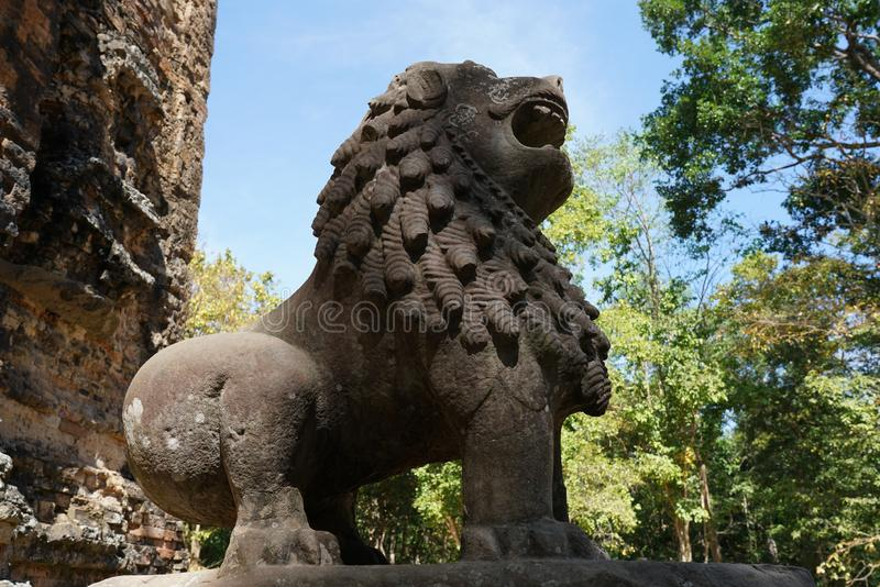 A statue of lion at Prasat Tao in Sambor Prei Kuk in Cambodia. Kampong Thom, Cambodia-January 12, 2019: A statue of lion at Prasat Tao in Sambor Prei Kuk in royalty free stock images
