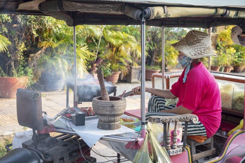 Kampot,柬埔寨- 2018年4月12日:烹调在街道厨房的高棉妇女肉kebab 柬埔寨streetfood小餐馆 库存图片