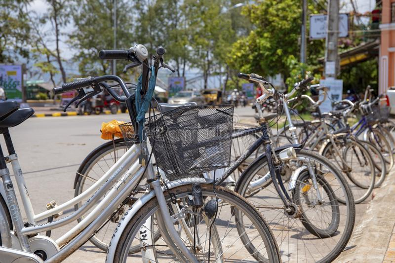 Kampot, Cambodia - 12 April 2018: city bicycles for rent closeup, sunny street on background. Modern urban bicycle stock images