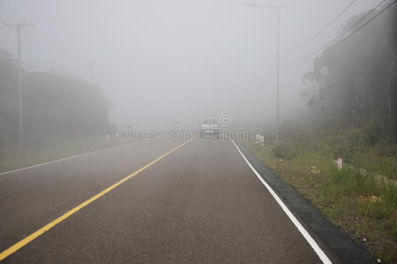 Kampot, Cambodia - 12 April 2018: misty road landscape and car. Dangerous driving in mist. White clouds on highway stock photography