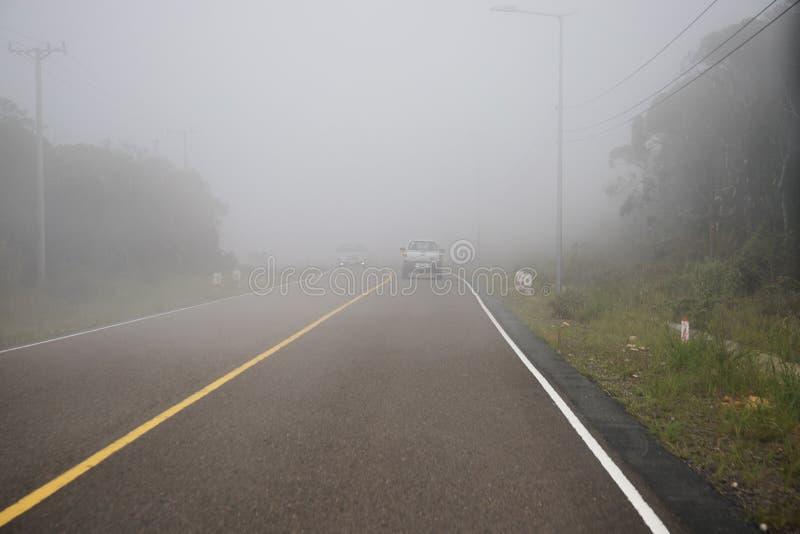 Kampot Cambodja - 12 April 2018: dimmigt väglandskap och bil Farlig körning i vita moln för mist på huvudvägen arkivbild