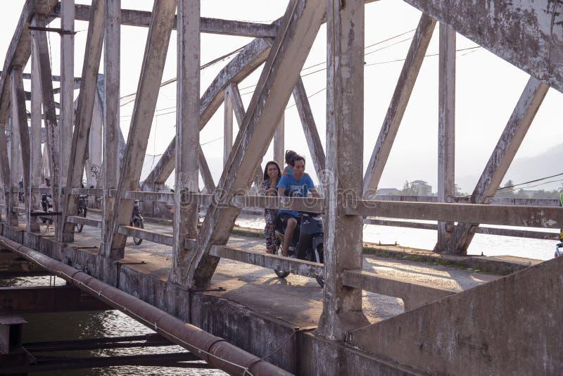Kampot Cambodja - 12 April 2018: en khmerfamiljen kör mopeden på den gamla bron Asiatisk familj med ungen på mopeden royaltyfri fotografi