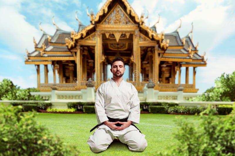 Kampsporter kämpe i yoga poserar, kloster arkivfoto