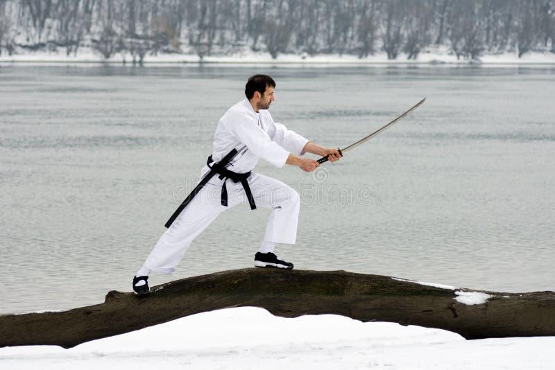 Kampsporter med svärdet på vintern fotografering för bildbyråer