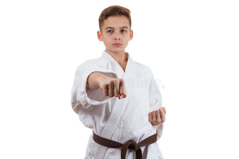 Kampsportsportkarate - tonårig pojke för barn i det vita kimonoutbildningsstansmaskin och kvarteret royaltyfria bilder