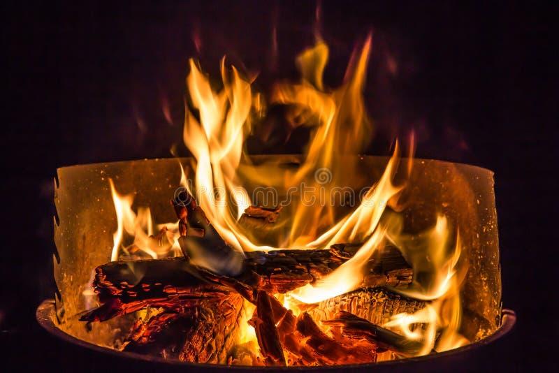 Kampvuur met brandhout het branden in een koperslager stock fotografie