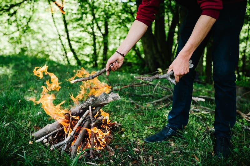 Kampvuur op de aard De handen van de mens `s Brandhoutvoorbereiding voor brand stock afbeelding