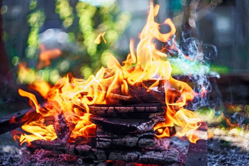 Kampvuur van houten stapel met vlamtongen die bij de zomerzonsondergang bij platteland branden Natuurlijke brandachtergrond stock foto