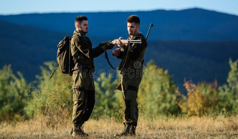 Kamratskap av manjägare Militärt enhetligt mode Arméstyrkor kamouflage Jaktexpertis och vapenutrustning hur royaltyfri bild