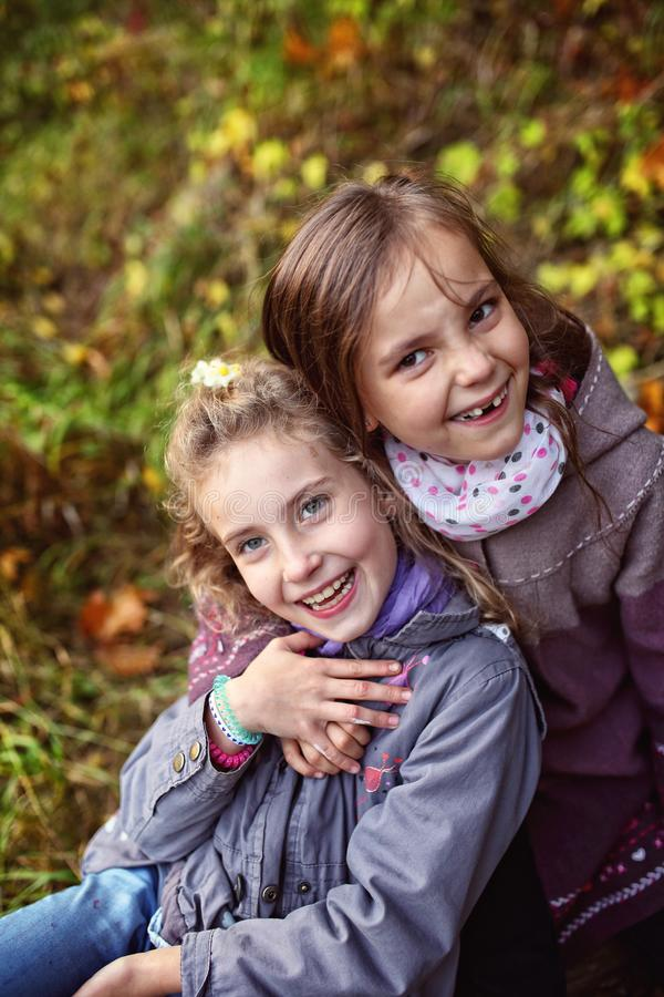 Kamratskap av två unga flickor i höstdag royaltyfri foto