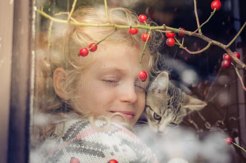 Kamratskap mellan flickan och katten bak fönster royaltyfria foton