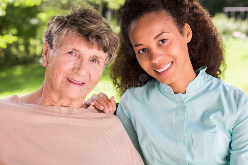 Kamratskap mellan pensionären och sjuksköterskan arkivfoto