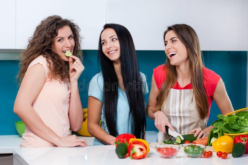 Kamratskap och sund livsstil som hemma lagar mat royaltyfri fotografi