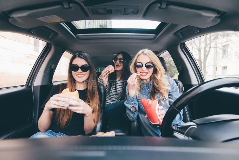 Kamratskap och tid tillsammans på vägen Tre barn och skönhetkvinnor har gyckel som äter tillsammans snabbmat och, kör en bil i vä arkivbild