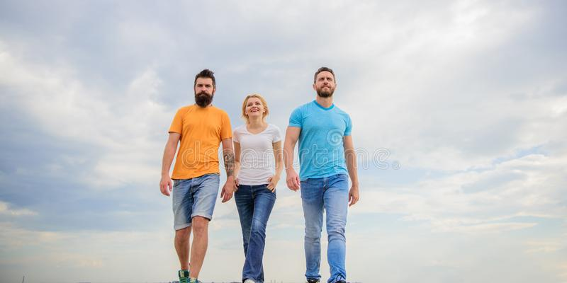 Kamratskap som testas för år Riktiga vänner för enig threesome Män och kvinnan går dramatisk bakgrund för molnig himmel riktigt arkivfoto